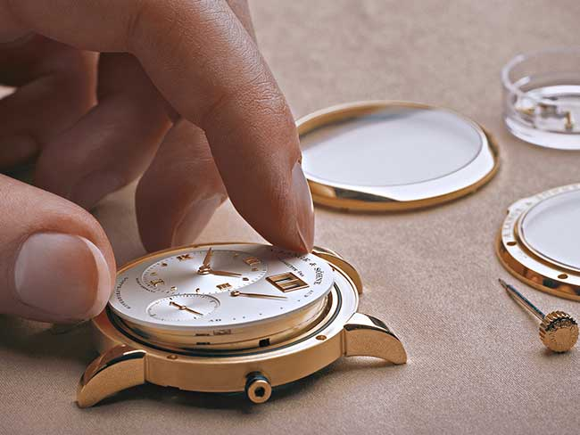 A watchmaker checks and assembles all parts of the watch before it is forwarded to the final inspection point