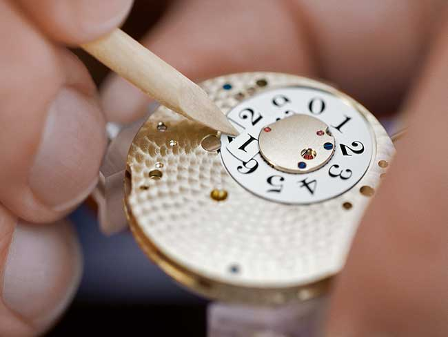 A watchmaker checks the oscillation timing and thus the rate accuracy of a movement