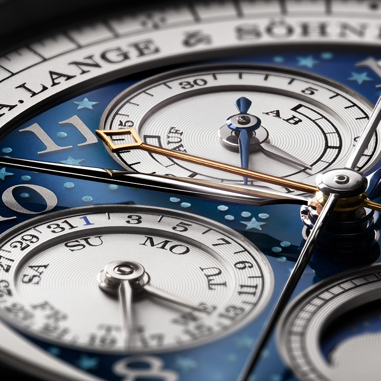 A close-up of the engraved stars beneath dark blue enamel on the dial of the 1815 RATTRAPANTE PERPETUAL CALENDAR HANDWERKSKUNST.