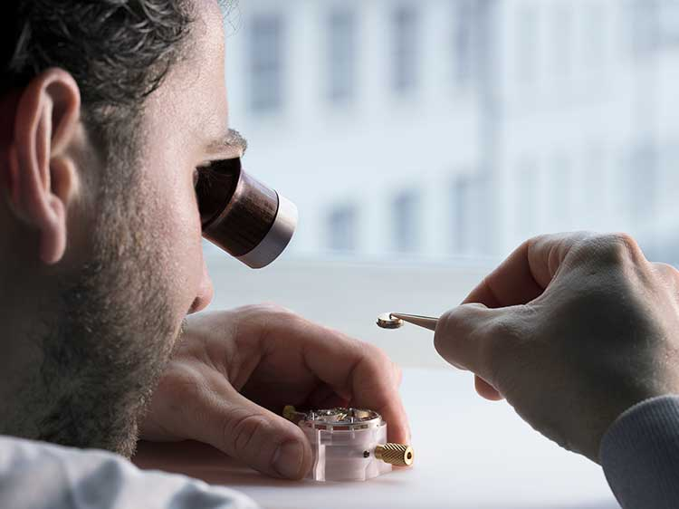A watchmaker inspecting a small part of a manufacture calibre with a watchmaker's magnifier