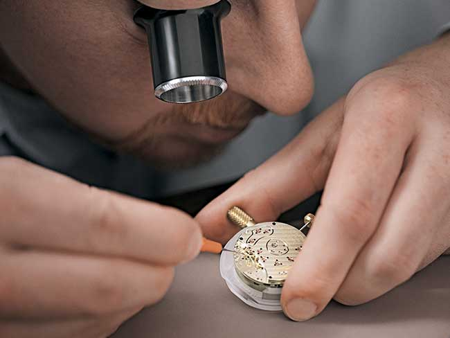 A watchmaker inspects the parts and function of a movement