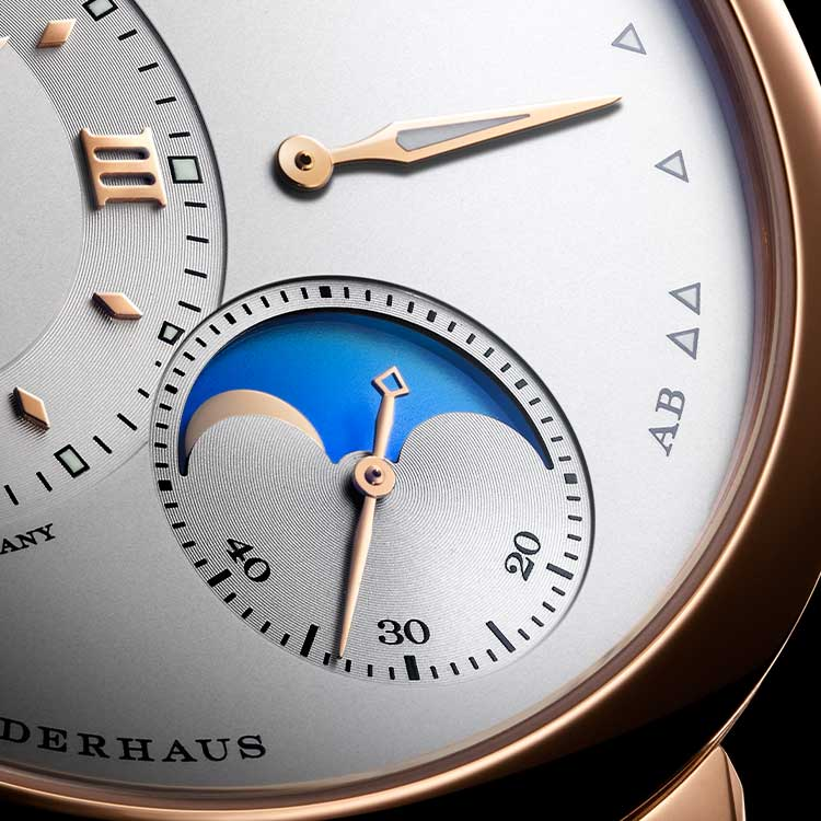 During the day, the moon on the LANGE 1 MOON PHASE appears against a light blue celestial disc with no stars.