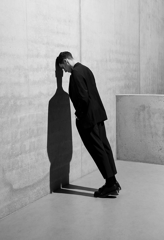 Black and white photography of a man leaning his head against a concrete wall. Clemens Poloczek for A. Lange & Söhne.
