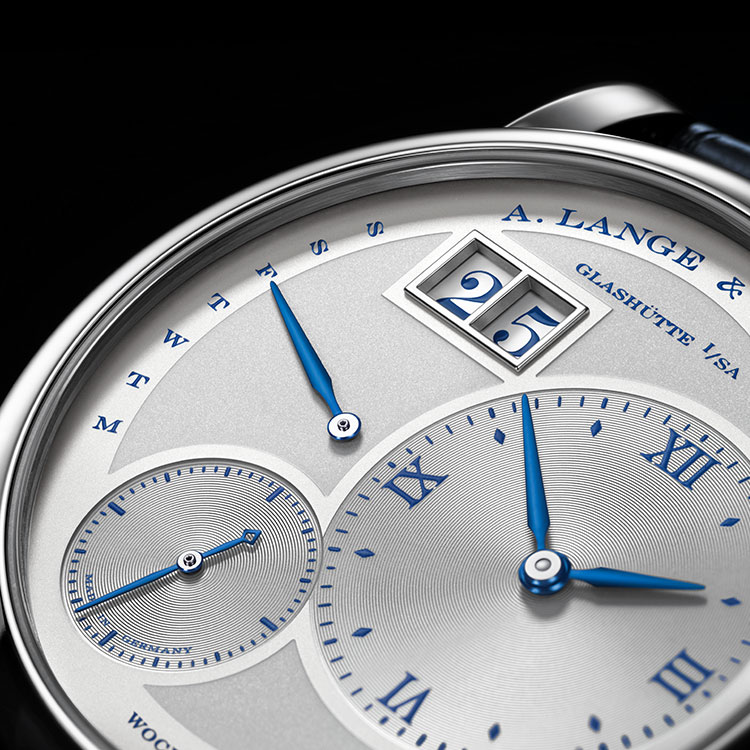 "Dial detail of the LANGE 1 DAYMATIC ""25th Anniversary"" in white gold with blued hands and a blue printed dial."