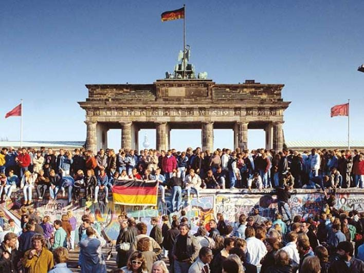 A section of the wall in Berlin in front of the Brandenburg Gate shortly after the transition. Many people sitting and standing on the wall wave German flags.
